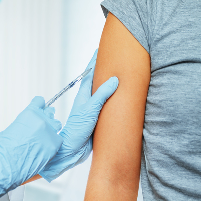 Doctor makes vaccination in the shoulder of patient in a hospital